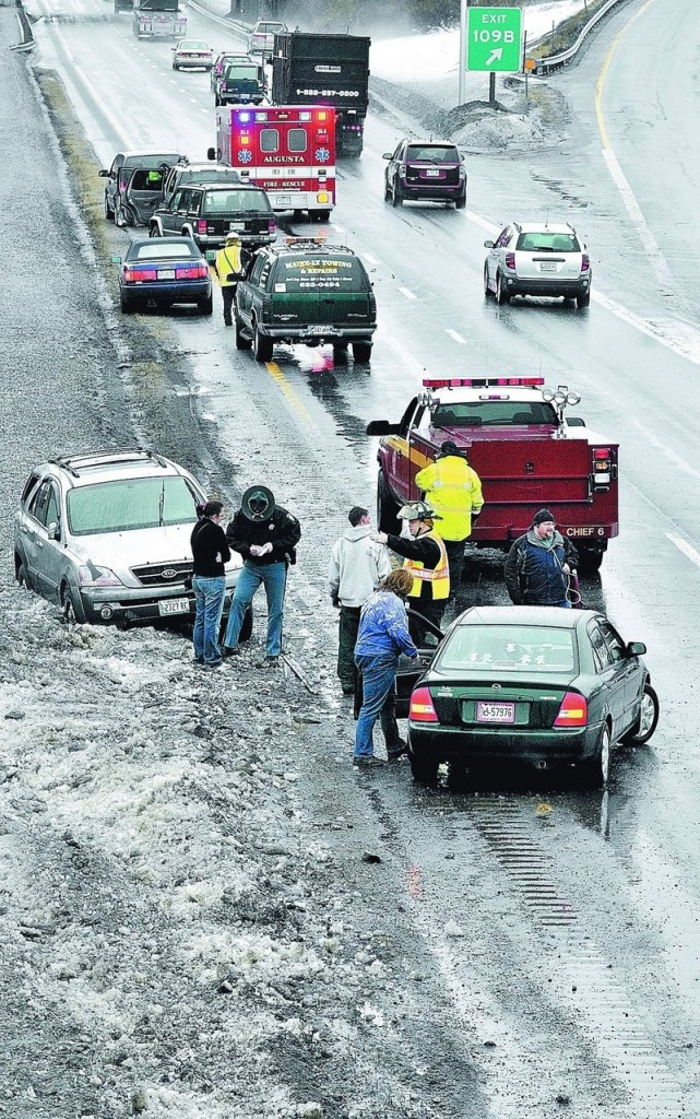 Augusta firefighters and paramedics and a State Police trooper work with people involved in accidents caused by an unusually large pothole in the southbound lane of Interstate 95 near exit 109B on Friday afternoon in Augusta. Staff photo by Joe Phelan Augusta firefighter/paramedics and a State Police trooper work with people involved in accidents in the south bound lane of Interstate 95 near exit 109 B on Friday afternoon in Augusta.