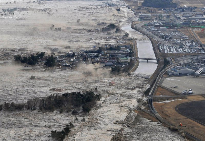 Earthquake-triggered tsunamis sweep the shore along Iwanuma in northern Japan on Friday.