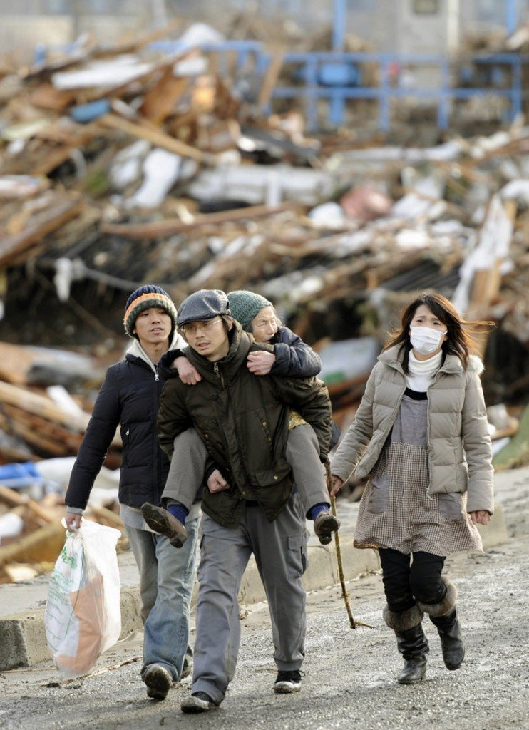 A family walks past flattened houses in Sendai, Miyagi Prefecture on Saturday morning, after Japan's strongest recorded earthquake slammed its eastern coast Friday.