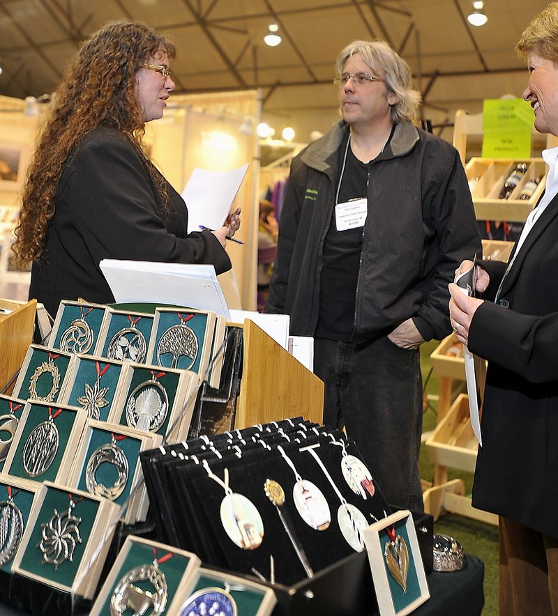 Julie Leighton, left, store manager at the Seashore Trolley Museum in Kennebunkport, and her husband, Glen, talk with Sharon Duffield, of Lovell Designs in Portland, about Lovell Designs' products at the New England Products Trade Show.
