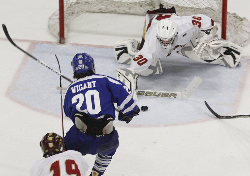 Thornton Academy goalie Jay Finch bends to knock away a shot by Ben Wigant of Lewiston in the second period of the Class A boys' hockey state championship game Saturday night at Lewiston. Thornton won 4-3 in double overtime, earning its first state title.