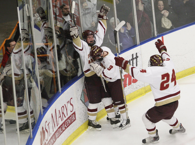 Sam Canales of Thornton Academy celebrates with C.J. Maksut, 3, and Tyler Danley, 24, after scoring Saturday night in the second period of the Class A final against Lewiston.