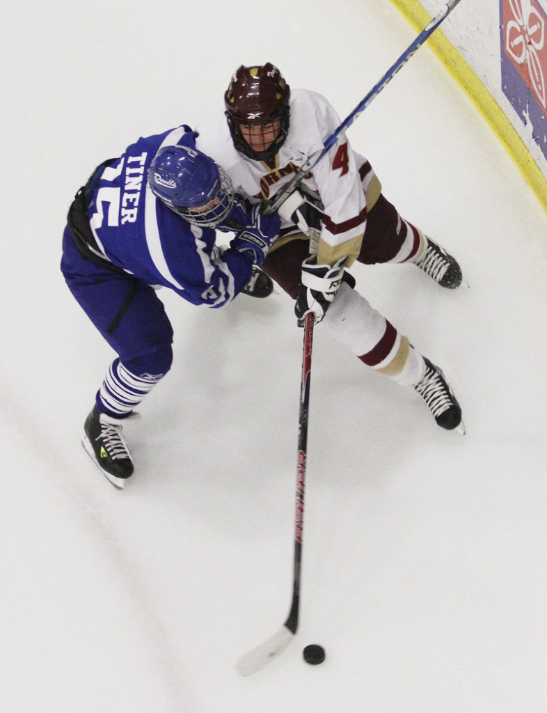 Andrew Carignan of Thornton Academy attempts to find a way around Brandon Tiner of Lewiston and retain the puck in the first period.