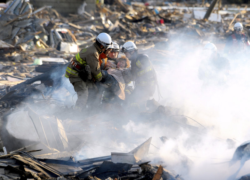 A resident is rescued from debris in the northern Japanese city of Natori on Saturday, one day after the powerful magnitude-8.9 quake struck.