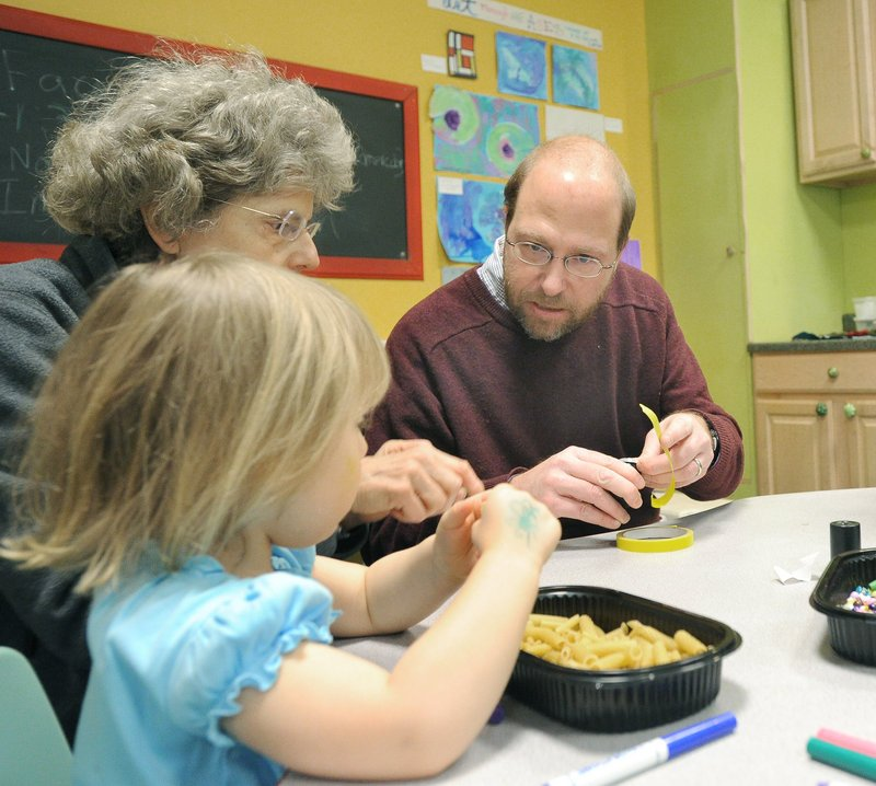Reporter Ray Routhier creates noisemakers with Ginny Grabowski and her granddaughter, Gianna Grabowski, 3,