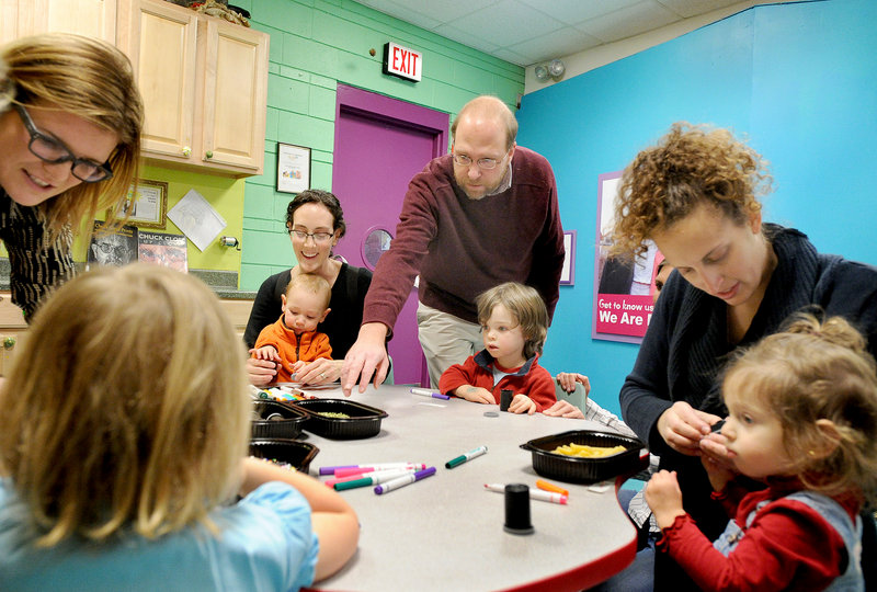 Reporter Ray Routhier works with 2-year-old Elias Botefield and other children creating noisemakers at the Children's Museum & Theatre of Maine in Portland.