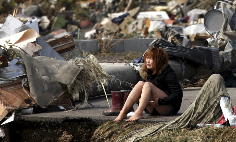 A woman breaks down Sunday amid debris left by Friday's earthquake and tsunami in Natori, in northern Japan. In the town of Minamisanrikucho, 10,000 people – nearly two-thirds of the population – have not been heard from since the tsunami wiped it out.