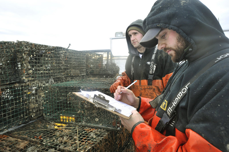 Lucky Catch sternmen Dave Laliberte, right, and Brian Rapp record ownership information on the lobster traps recovered Monday.