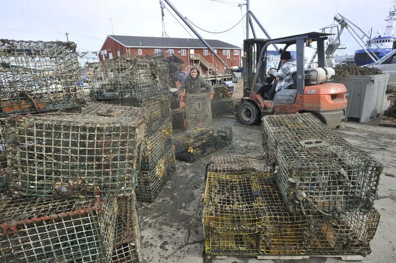 Retrieved lobster traps are unloaded onto the Portland Fish Pier. One boat recovered 60 traps Monday, and the boats will be going out again today.