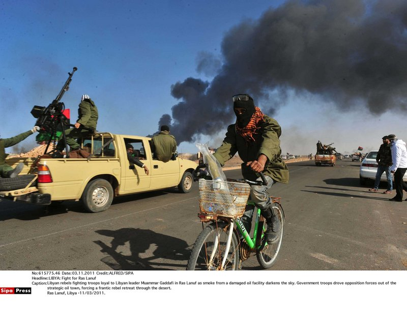 Libyan rebels fire on troops loyal to Libyan leader Moammar Gadhafi in Ras Lanuf as smoke from a damaged oil facility darkens the sky. Government troops drove opposition forces out of the strategic oil town, forcing a frantic rebel retreat through the desert.