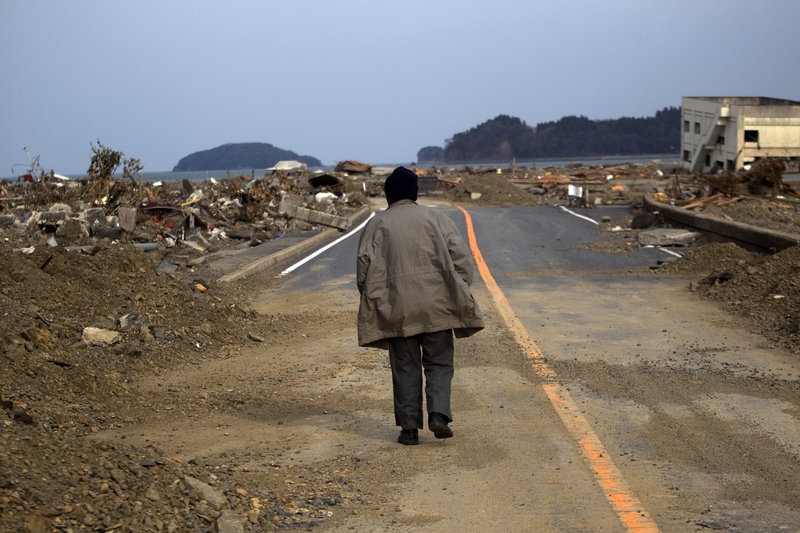 A survivor of the Japanese earthquake and tsunami walks alone on a road past the destroyed village of Saito, in northeastern Japan, on Monday. The tsunami that devastated Japan's coast rolled in through a tree-lined ocean cove and obliterated nearly everything in its path, wiping out the village of about 250 people and 70 houses.