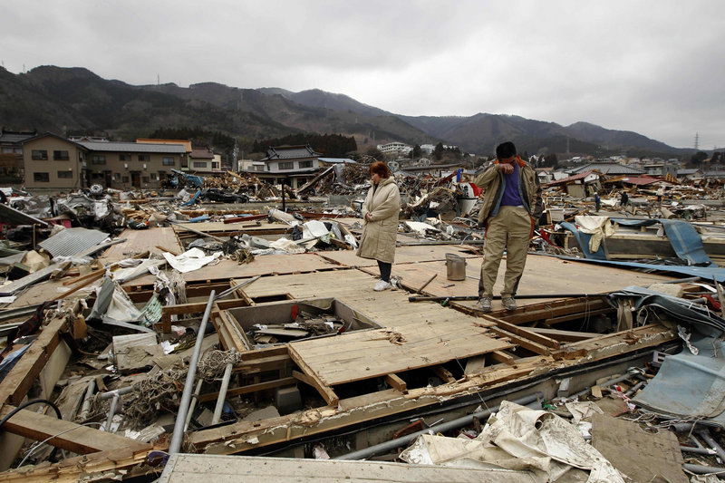 Keijo Nakamura, right, and his wife, Haruka, stand Tuesday in Ofunato, Japan, on the remains of a dead relative's home, which had been washed away by last Friday's tsunami. The U.S. and United Kingdom deployed 220 rescue team members to the town to hunt for trapped survivors Tuesday.
