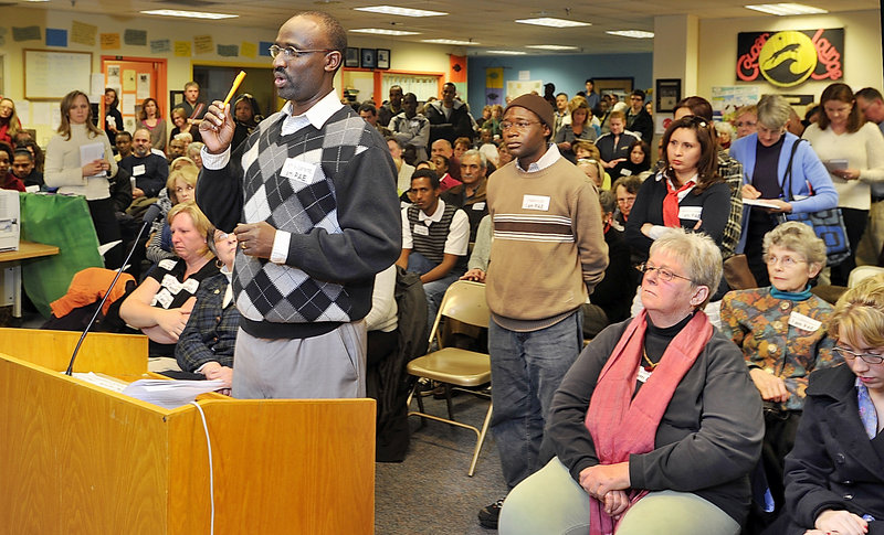 In a room full of concerned teachers, students, parents and others, the executive director of Community Financial Literacy, Claude Rwaganje, speaks in support of Portland's adult education program Tuesday night.