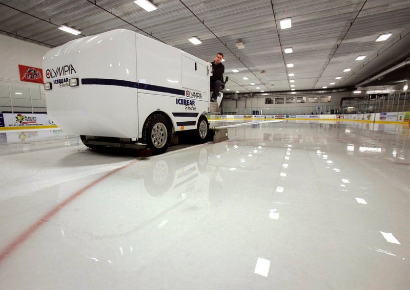 Rob Carrier resurfaces the ice at the Portland Ice Arena using an electric Olympia machine. The electric resurfacer, as opposed to a propane-powered machine, guarantees the absence of fumes that have been harmful to players and customers in other rinks around the country.