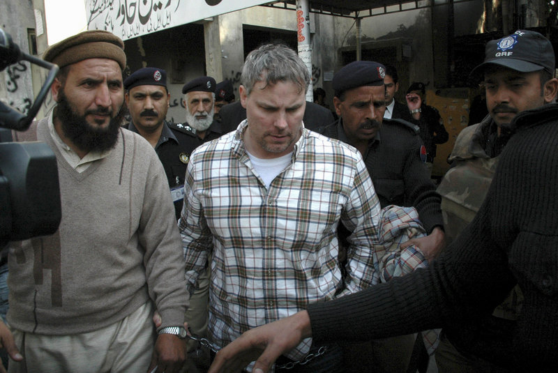 Pakistani security officials escort Raymond Allen Davis, center, on Jan. 28 to a court in Lahore. The CIA contractor was released Wednesday after families of the two Pakistanis he killed pardoned him in exchange for compensation.