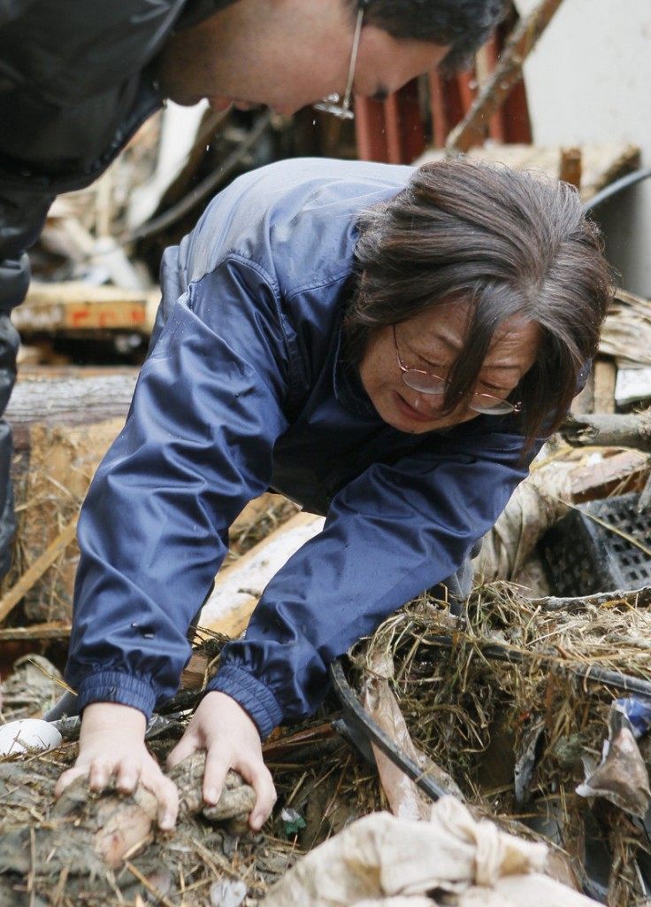 Yoshie Murakami weeps Wednesday as she holds her deceased mother's hand in the rubble near where her home used to stand in Rikuzentakata, Japan.