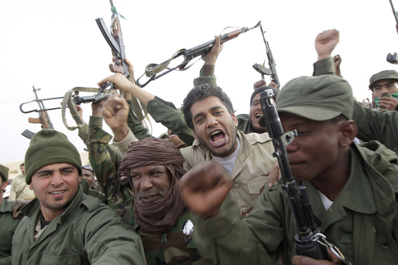 Libyan soldiers celebrate Wednesday before advancing on the city of Ajdabiya. The image was taken on a trip organized by the government for a small group of journalists.