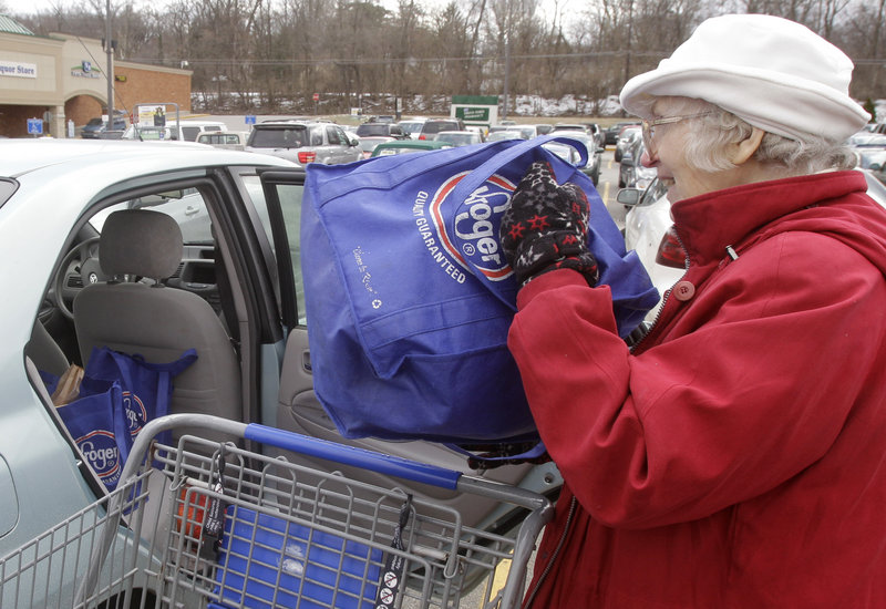 Lynne Curtiss places reusable Kroger bags in her car after shopping in Cincinnati. The grocery chain has eliminated a bonus for shoppers using their own bags.