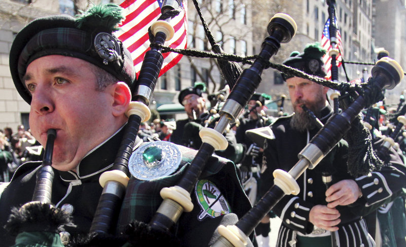Joseph O'Keefe, left, plays a bagpipe as the Department of Sanitation of New York's Emerald Society Pipes and Drums marches during the St. Patrick's Day parade a year ago in New York. St. Patrick's Day is taking on added meaning this year, as Irish-Americans have a long history of involvement in the labor movement.