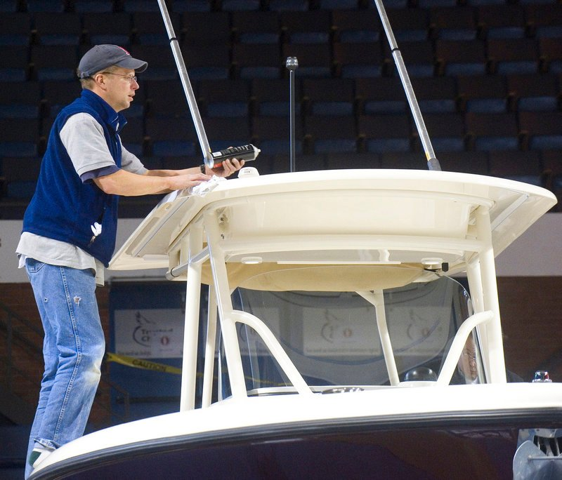Mike Sullivan, from the Yarmouth Boat Yard, puts the finishing touches on the hardtop of a 28-foot Pursuit powerboat before the show opens Friday.