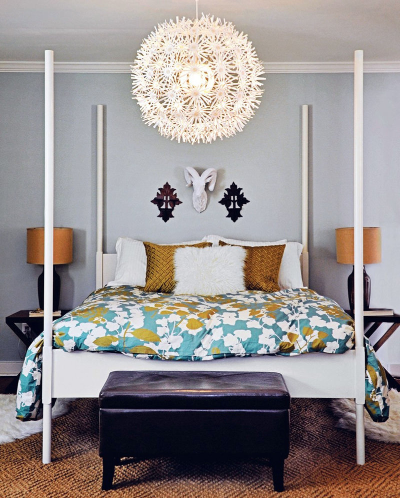 An Ikea bed and light fixture take center stage in the master bedroom at the Petersiks' house. West Elm bedding, a Pottery Barn area rug (both bought on sale) and Target side tables round out the space.