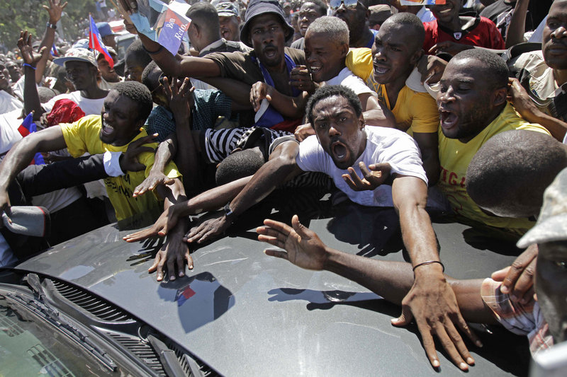 Energized supporters of Haiti's former president, Jean-Bertrand Aristide, surround his car as Aristide arrived at his home in Port-au-Prince, Haiti, on Friday, after seven years in exile.