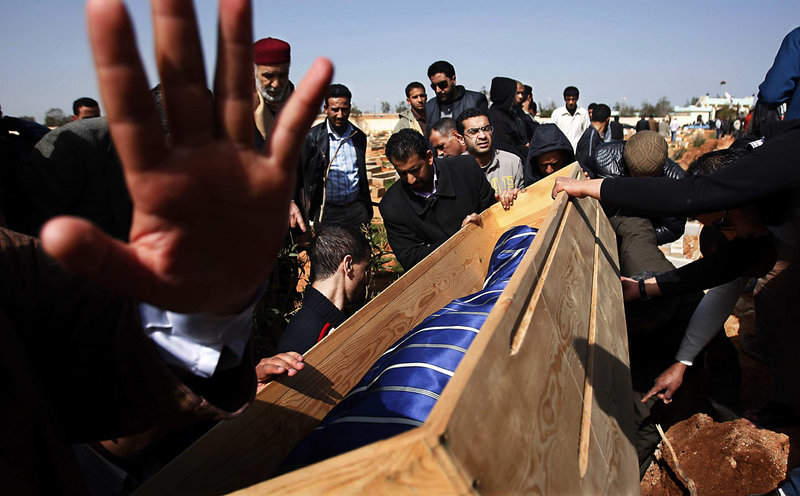 Mourners lower the body of a man into a grave in Benghazi, Libya, earlier this month. The man succumbed to wounds suffered Feb. 17, at the start of an uprising against Libyan dictator Moammar Gadhafi. Many believe the courage to rebel came from the daring shown in early protests of the 1996 killings of inmates in a Tripoli prison.