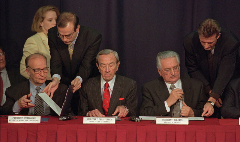 Then-Secretary of State Warren Christopher, center, is flanked by Bosnian President Alija Izetbegovic, left, and Croatian President Franjo Tudjman as they sign the Dayton peace accord on Nov. 10, 1995. Christopher died Friday at age 85.