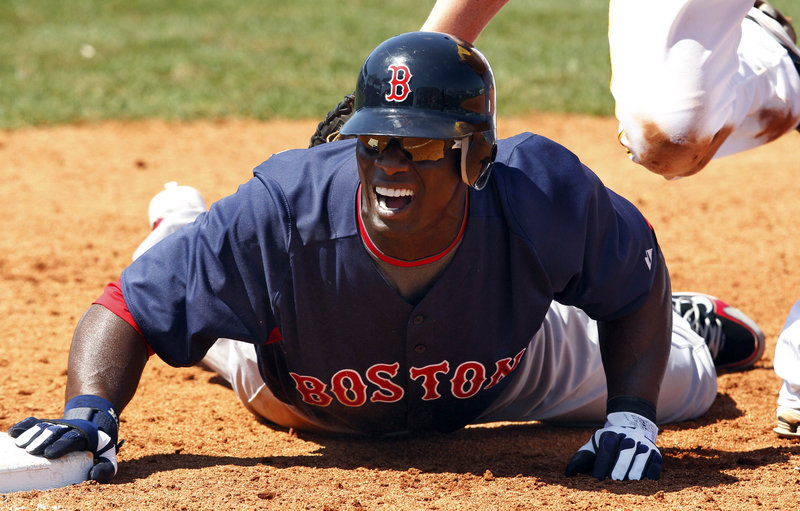 Boston outfielder Mike Cameron dives back to first base in the sixth inning of Saturday's spring-training game against the Pittsburgh Pirates in Bradenton, Fla. Pittsburgh won 7-5. Red Sox starter Josh Beckett took the loss.