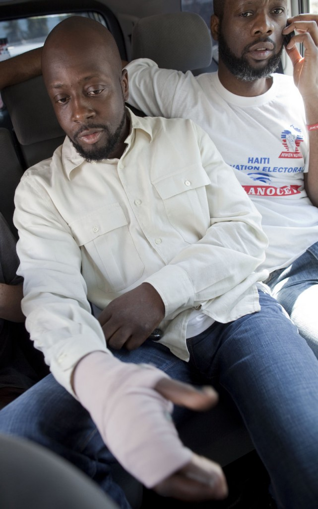 With a bandage on his right hand, singer Wyclef Jean sits in a car before casting his ballot at a polling station on Sunday.