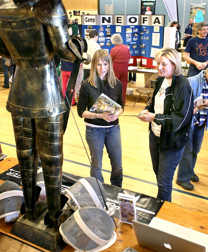 Nancy Reynolds, right, owner of Fencing Youth Camps in Westbrook, talks to Tennyson Towl of South Portland during the camp fair Sunday at Portland's East End School. Parents and children had the chance to visit with representatives of 70 camps and summer programs.