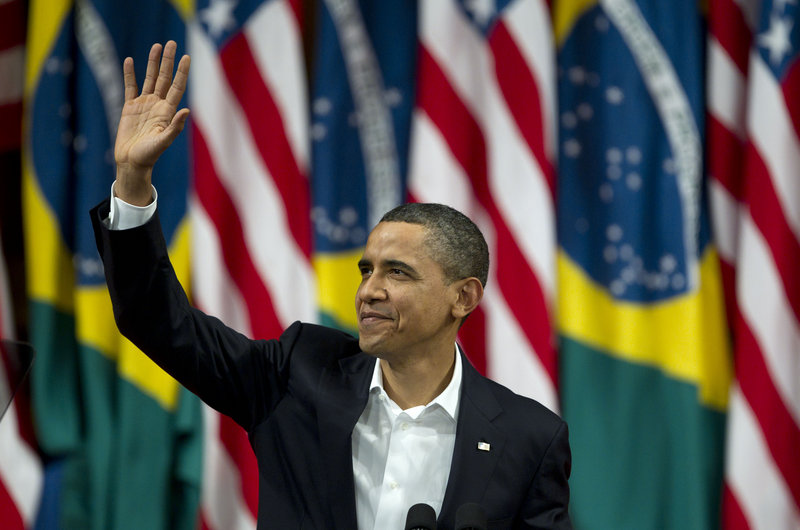 President Obama waves before giving a speech at the Municipal Theater in Rio de Janeiro, Brazil, on Sunday. He praised Brazil for moving millions into its middle class and embracing human rights, underlining that point as unrest sweeps the Middle East and north Africa.
