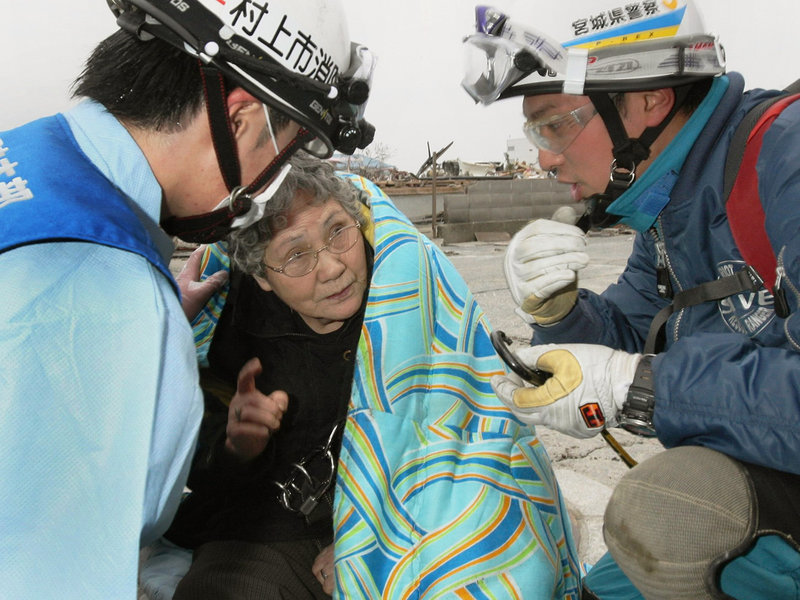 Sumi Abe, 80, speaks to firefighters in Ishinomaki, Miyagi prefecture, in northeastern Japan on Sunday. Abe and her grandson Jin were rescued after the teenager pulled himself out of their flattened house and alerted rescuers.