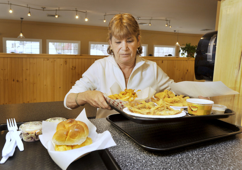 Brenda Mershimer prepares to serve several lunch orders fresh from Docks' kitchen. Besides seafood, Docks serves burgers, chicken, kids' meals and more.