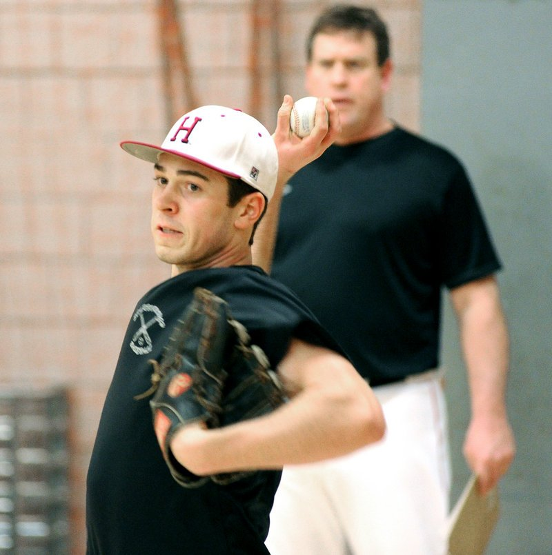 Senior Ryan Mancini delivers a pitch as Coach Mike Coutts looks on Monday at Scarborough. A wrist injury kept Mancini from pitching last spring.