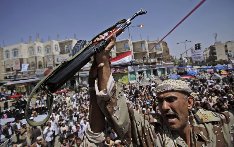 A Yemeni army officer holds up his AK-47 as officers joined protesters demanding the resignation of Yemeni President Ali Abdullah Saleh in Sanaa, Yemen, on Monday.