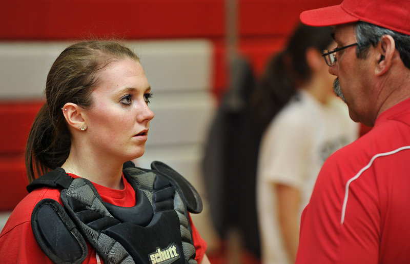 South Portland catcher Katlin Norton listens to instructions from Red Riots softball coach Ralph Aceto on Monday. Pitchers and catchers get a week to limber up before teammates join them for tryouts and practice.