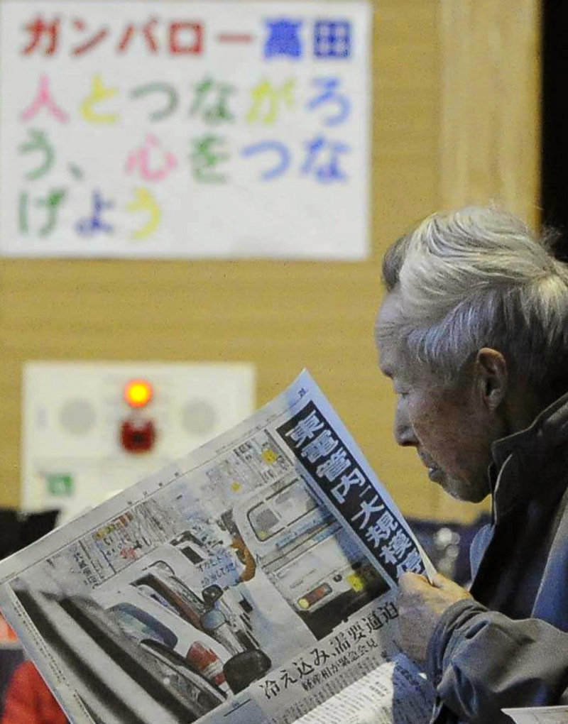 An elderly woman reads a newspaper at an evacuation center in Rikuzentakata, Iwate prefecture, in northeastern Japan, on Friday. Lacking access to modern media, and with residents in need of information, one newspaper, the Hibi Shimbun in Ishinomaki, wrote its articles by hand with black felt-tip pens on big sheets of white paper. It missed publication only for two days after the earthquake and tsunami.