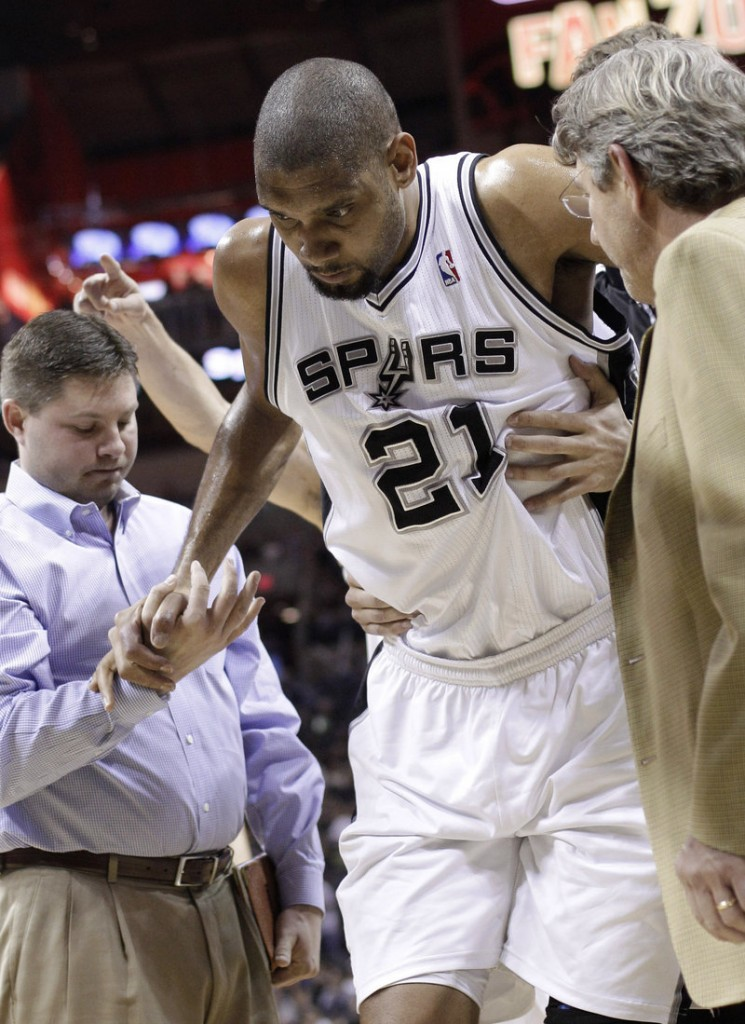 Tim Duncan is helped off the court after spraining his left ankle Monday. He'll miss at least three games in the Spurs' stretch drive.
