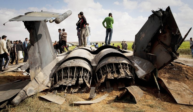 Libyans inspect the wreckage of an American F-15 fighter jet after it crashed in a field in eastern Libya overnight Monday. The U.S. said both crew members ejected safely and were rescued after what was believed to be a mechanical failure.