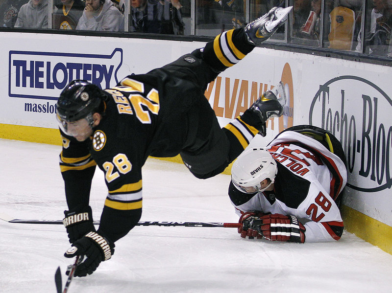 Bruins left wing Mark Recchi goes flying over New Jersey defenseman Anton Volchenkov during division-leading Boston's 4-1 win at home on Tuesday.