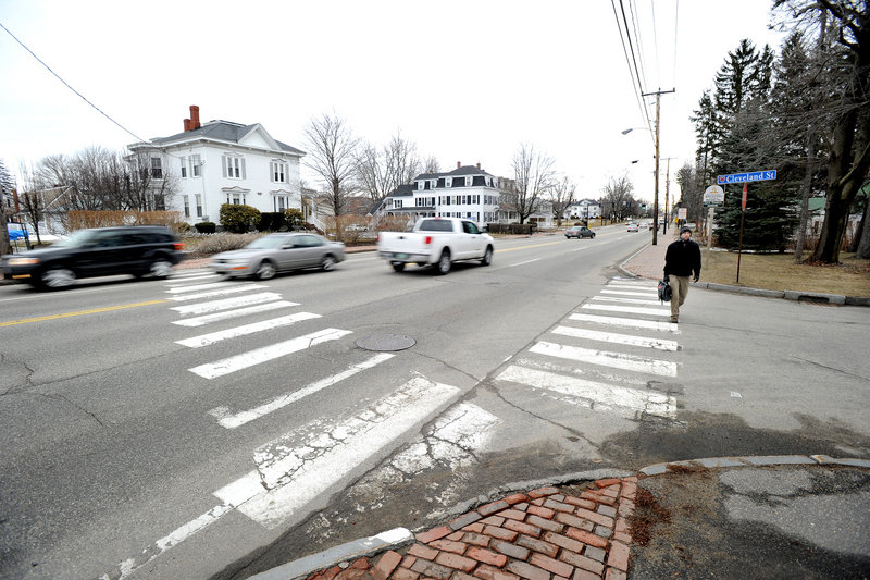 The crosswalk at Cleveland Street in Saco, left, where a pedestrian was struck and killed by a minivan last summer, crosses a four-lane stretch of Main Street traveled by 25,000 vehicles a day. This crosswalk and one at nearby Summer Street will be removed as soon as weather permits.