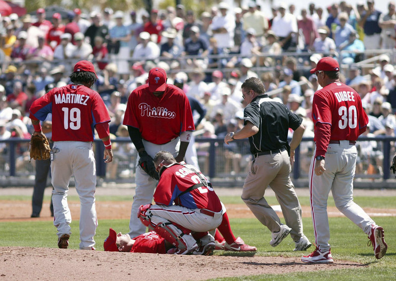 Teammates and trainers rush to pitcher Roy Oswalt after he was struck on the neck by a line drive by Tampa Bay's Manny Ramirez in an exhibition game Wednesday in Port Charlotte, Fla. An MRI showed Oswalt only suffered a bruise.