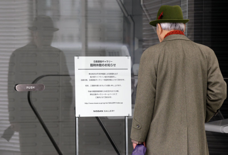 A man reads a notice announcing that a Nissan showroom in Tokyo is closed temporarily because of the March 11 earthquake and tsunami. Nissan is studying whether to have its Dechard, Tenn., plant supply six-cylinder engines to Japan.
