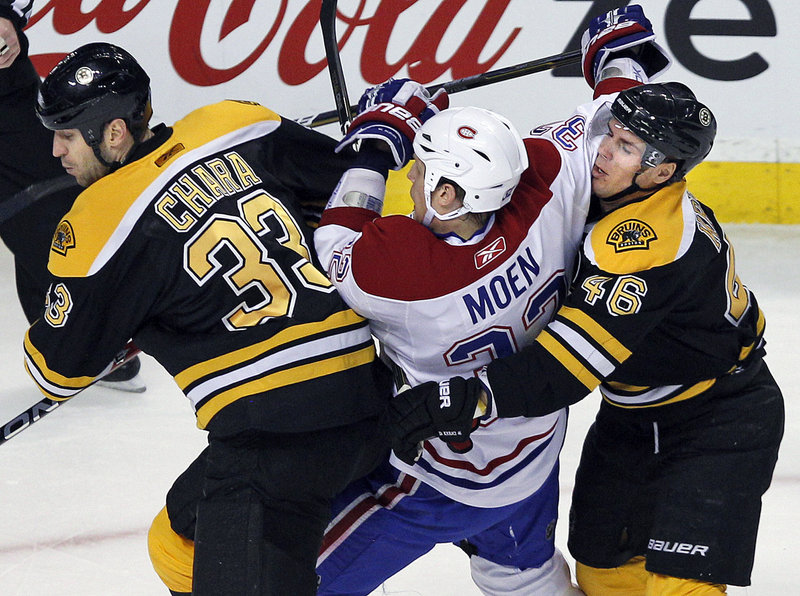 Boston teammates Zdeno Chara, left, and David Krejci sandwich Montreal's Travis Moen at the TD Garden on Tuesday night. The win gives Boston a five-point lead on Montreal in the Northeast Division.