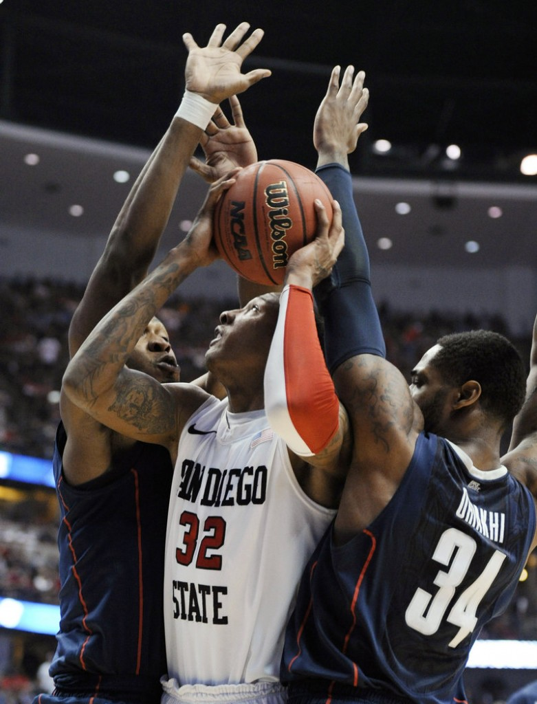 Billy White of San Diego State tries to put up a shot as Connecticut's Charles Okwandu, left, and Alex Oriakhi defend during the Huskies' 74-67 win Thursday in Anaheim, Calif.