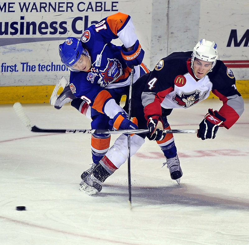 Corey Tropp, right, of the Pirates and Bridgeport's Rhett Rakhshani collide and the puck slides away during their game Friday night at the Civic Center. The Sound Tigers won on the road for just the seventh time this season.