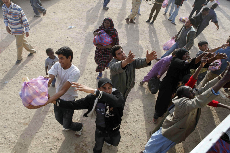 Libyans catch bread donations in the city of Ajdabiya in eastern Libya on Saturday.