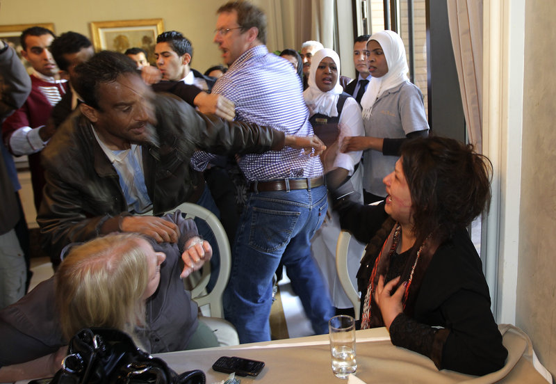 A Ministry of Information official, left, tries to grab Iman Al-Obeidi, right, as she tells reporters that she was sexually assaulted by Libyan troops after being detained at a checkpoint in Tripoli, Libya.