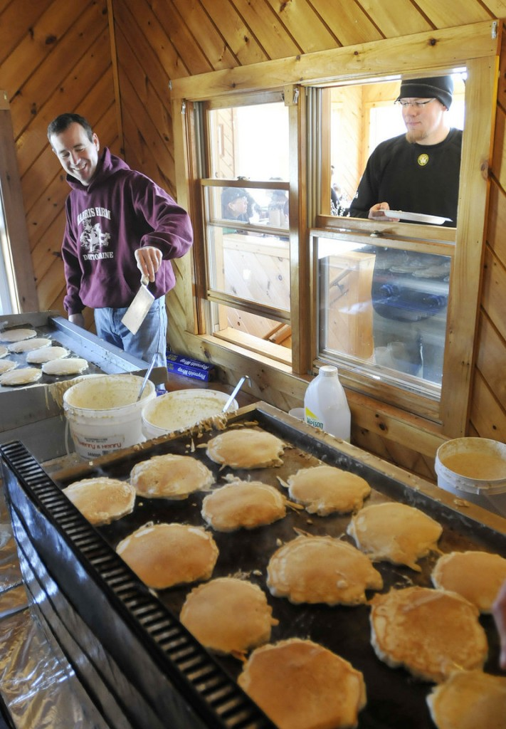Clint Harris cooks pancakes as Denis Clark of Saco awaits a second helping at a window during Maine Maple Sunday at Harris Farm in Dayton on Sunday.